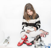 fashionable boring little girl sitting and looking at her shoes collection Stock Photo