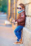 Fashionable boy with digital tablet near the wall Royalty Free Stock Images