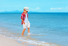 Fashionable boy, kid playing in waves on summer beach Stock Image