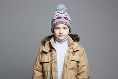 Fashionable Boy in winter outerwear. knitted hat stock images