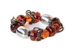 Fashionable bracelet. Modern bracelet of transparent and dark glass beads isolated on white stock photography