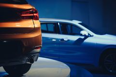 Fashionable bright auto show A number of new cars parked in the car dealers` warehouse, modern design of the premises.  Royalty Free Stock Images