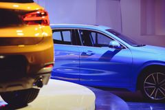 Fashionable bright auto show A number of new cars parked in the car dealers` warehouse, modern design of the premises.  Royalty Free Stock Photos