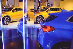 Fashionable bright auto show A number of new cars parked in the car dealers` warehouse, modern design of the room with mirrors.  royalty free stock photo