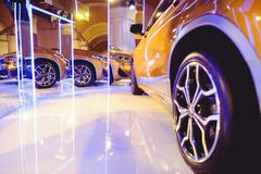 Fashionable bright auto show A number of new cars parked in the car dealers` warehouse, modern design of the room with mirrors.  stock photos