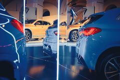 Fashionable bright auto show A number of new cars parked in the car dealers` warehouse, modern design of the room with mirrors.  Royalty Free Stock Photos