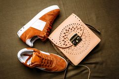 Brown suede sneakers with white accents on a white sole and a brown leather bag with a golden lock on a green woven background royalty free stock photography