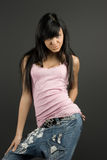 Fashionable brunette. Young and fashionable brunette posing in pink t-shirt and blue jeans royalty free stock image