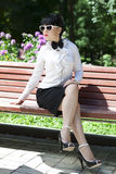 Fashionable  brunette on a bench Stock Photos