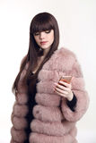 Fashionable brunette girl in pink fur coat holding mobile phone. Isolated on white background. Trendy hairstyle. Brown haired Stock Photography