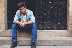 Fashionable brunette hair man sitting in a urban setting Royalty Free Stock Photography