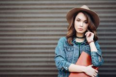 Fashionable brunette in hat, jeans jacket and choker on neck. Fashionable brunette in brown hat, jeans jacket and choker on neck posing at street,looking at stock photo