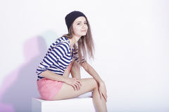 Fashionable Brunette in Hat and Striped Shirt Posing in Studio Against White. Royalty Free Stock Image