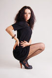 Fashionable brunette in a little black dress royalty free stock photo
