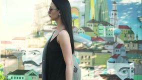Fashionable brunette in sunglasses walking in slow motion against graffiti wall. Elegance stylish woman in sunglasses, black dress and grey coat is walking at stock video footage