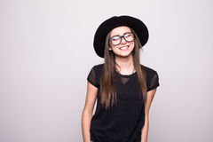 Fashionable brunette wearing bright black clothes holding her hat with eyesglasses  on grey Stock Photography