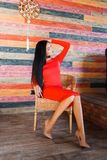 Fashionable brunette woman with long hair and red dress sitting on a chair at home and looking away stock photos