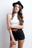 Fashionable brunette woman with long slim legs posing in studio. Stock Photography