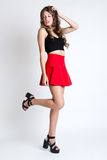 Fashionable brunette woman with long slim legs posing in studio. Royalty Free Stock Photos