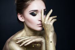 Fashionable Brunette Woman Model with Creative Makeup. Smoky Eyes Make Up with Gold and Black Eyeshadow royalty free stock photography