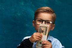 Fashionable business child counting money. Closeup of cute fashionable business child counting money. Caucasian child wearing eyeglasses posing with cash on blue Royalty Free Stock Images