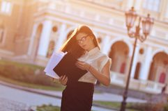 Fashionable business lady looks at paper forms. Portrait of a young brunette royalty free stock photo