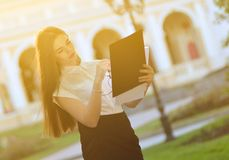 Fashionable business lady looks at paper forms. Portrait of a young brunette woman stock images