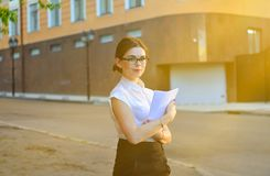 Fashionable business woman holding a blank of paper in her hands and posing on the camera. The working process. Portrait of a young brunette woman outdoor royalty free stock photos