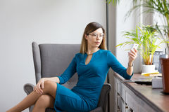 Fashionable business woman in round glasses sitting near window and looking to smartphone. Telephoto Stock Image