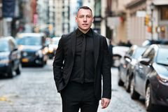 Fashionable businessman wearing black tie suit outfit walking on city street after working day.  royalty free stock photography