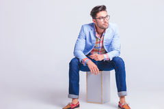 Fashionable businessman wearing glasses. Posing while seated on box looking away from the camera in studio background Stock Photos