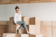 Fashionable businesswoman in formalwear sitting on wooden cubes. Beautiful fashionable businesswoman in formalwear sitting on wooden cubes Royalty Free Stock Images