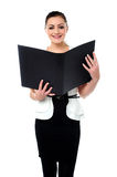 Fashionable businesswoman reviewing a file Stock Photo