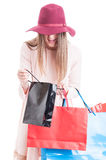 Fashionable caucasian woman looking inside black gift bag Royalty Free Stock Photos