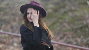 Fashionable cheerful young girl with long hair, purple hat and black coat walks down the street. Cloudy windy weather stock video
