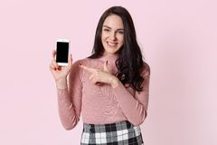Fashionable cheerful young woman holds new mobile phone, direct her forefinger to it, presentating purchase, looks happy. Delighted cute smiling model poses stock photo