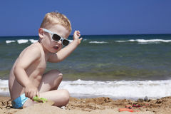 Fashionable Child plays on the beach in sand. litt Stock Photography