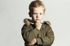 Fashionable child in winter coat. fashion kids.khaki parka.little boy hairstyle Stock Photos