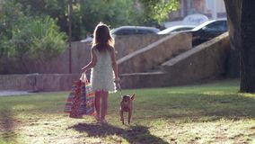 Fashionable childhood, stylish little girl with home animal walking outdoors after visit of boutiques and carry. Fashionable childhood, stylish child girl with stock video
