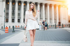 Fashionable city girl concept. Gorgeous young woman walking near city building wearing summer outfit clothes.  Royalty Free Stock Image
