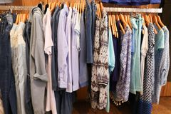 Fashionable clothes in a boutique store multicolored womens clothing hanging. On the hanger Stock Image