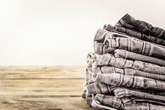 Fashionable clothes. pile of jeans on a wooden background. grain Stock Images