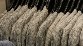 Fashionable collection of warm clothes. Large number of new warm stylish sweaters hanging on hangers in the clothing. Fashionable collection of warm clothes. A stock video footage