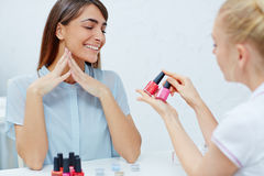 Fashionable colors. Beautician showing nail polishes to enthusiastic female in nailcare salon Royalty Free Stock Photography