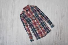 Fashionable concept. Checkered shirt on a wooden background. Fem. Ale wardrobe royalty free stock image
