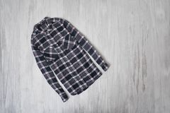 Fashionable concept. Checkered shirt on a wooden background. Fem. Ale wardrobe stock photo
