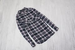 Fashionable concept. Checkered shirt on a wooden background. Fem. Ale wardrobe royalty free stock photo