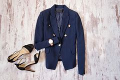 Fashionable concept. Classic blue jacket, watch and black shoes. Light wooden background Stock Photos