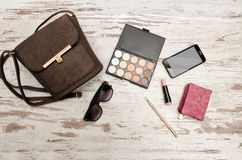 Fashionable concept: eyeshadows, handbag, glasses, mobile phone, lipstick, wallet on a wooden background. Royalty Free Stock Photography