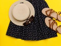 Fashionable concept. Female summer wardrobe. Straw hat and sundress, sunglasses, sandals. Yellow background Royalty Free Stock Image